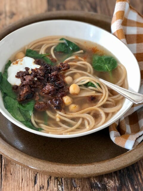 Aush, an Afghan noodle soup with chickpeas, spinach, ground meat, and yogurt with a spoon and checked napkin
