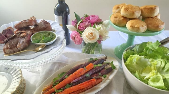 An Easter table set with lamb chops, carrots, biscuits, and other food with a white tablecloth