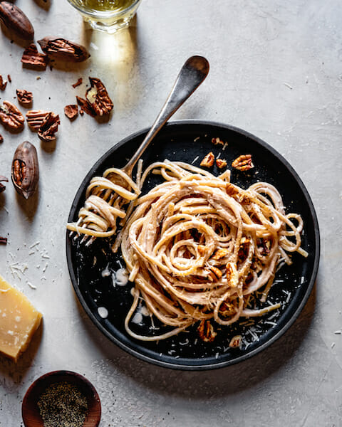 Linguine alfredo on a dark plate with a fork, parmesan, and pecans