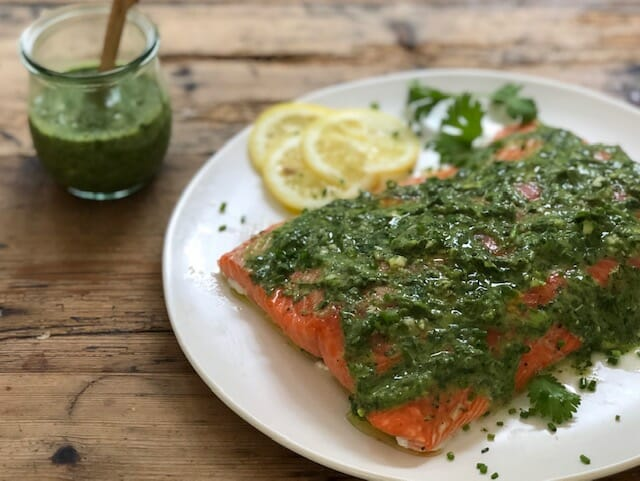 salmon served with green sauce on a white plate or summer vegetable salad served on a plate