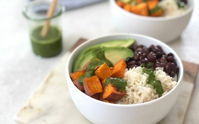 White bowl with sweet potato black beans avocado and a green sauce with a blue napkin