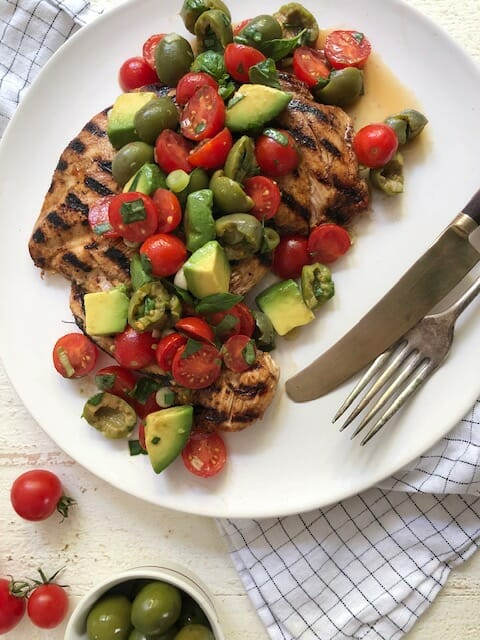 grilled chicken paillard on a white plate topped with tomato, olive, and avocado salad